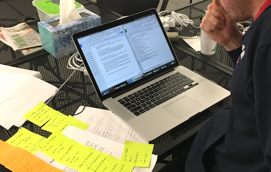 Person using a laptop with sticky notes and paperwork