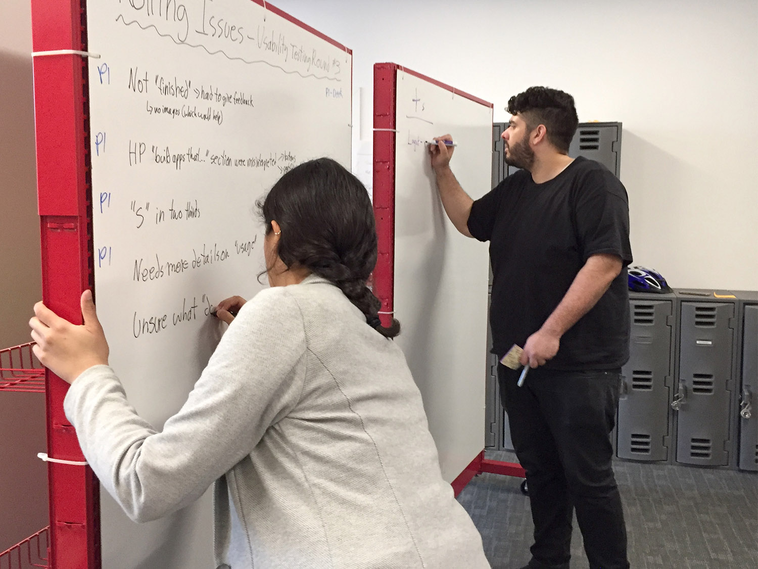 Two students writing analysis information on a whiteboard for other team members.